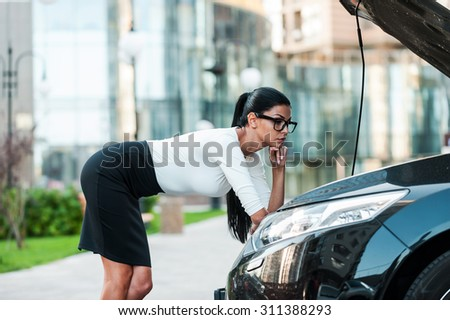 Car trouble. Seductive young businesswoman holding hand on chin while leaning at the opened vehicle hoodof her car - stock photo