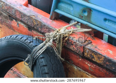Car tyre tied for protect bumping on boat - stock photo