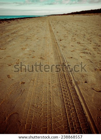 car tyre tracks on the beach sand in perspective - retro vintage 80's film look - stock photo