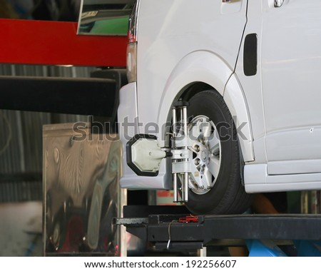 Car wheel fixed with computerized wheel alignment machine clamp. - stock photo