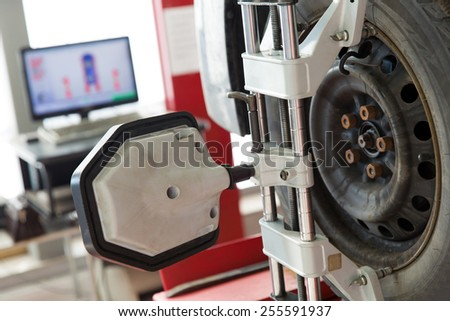 Car wheel with computerized alignment device at wheel and tire alignment service station - stock photo