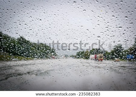 Car windshield covered with rain drops - stock photo