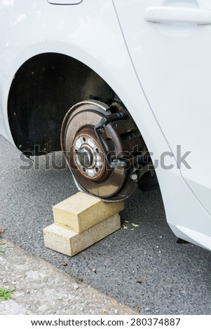 Car with stolen wheels. White vehicle left on wooden bricks. - stock photo