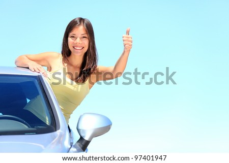 Car. Woman driver happy smiling showing thumbs up coming out of car window on blue summer sky above the clouds. Beautiful young mixed race Caucasian / Chinese Asian woman. - stock photo