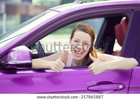 Car. Woman driver happy smiling showing thumbs up coming out of violet car side window on outside parking lot background. Beautiful young woman happy with her new vehicle. Positive face expression - stock photo