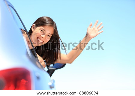 Car woman happy waving smiling at camera popping head out the window. New car, road trip vacation or drivers license concept. Beautiful young mixed race Chinese Asian / white Caucasian woman. - stock photo