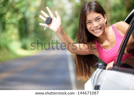 Car - woman showing new car keys smiling happy on road trip after getting drivers license. Beautiful young driving student coming excited out of window holding car key. - stock photo
