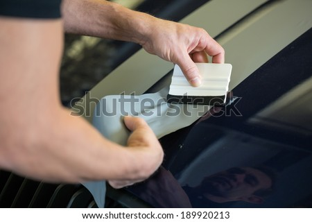 Car wrapper straightening wrapping foil with a squeegee to remove air bubbles - stock photo