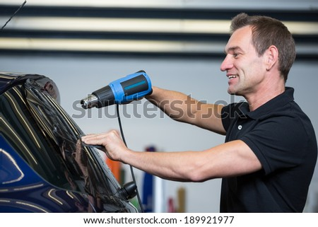 Car wrapping specialist attaching tinting foil to car window - stock photo
