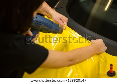 Car wrapping specialists using heat gun to prepare vinyl foil  - stock photo