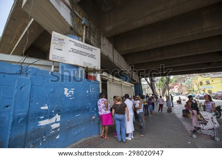 CARACAS, VENEZUELA, APRIL 20: Unidentified group of people waiting in line at a public supermarket doors in Caracas. With significant inflation, rationing is required in some cities in 2015 . - stock photo