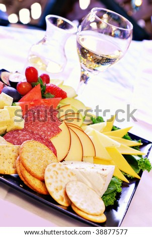 Carafe and glass of white wine with cheeseboard assortment - stock photo