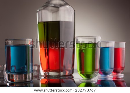 Carafe and glasses of multicolored alcohol drinks with ice - stock photo