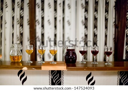 carafe and glasses of red and white wine at rustic or vintage cocktail party  - stock photo