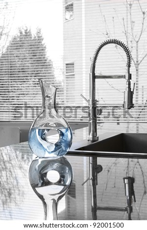 carafe of water in modern kitchen - partially toned image - stock photo
