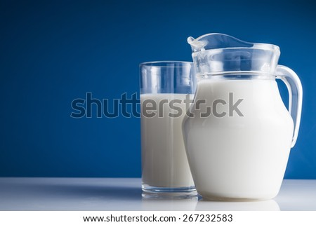 Carafe with milk on white table - stock photo