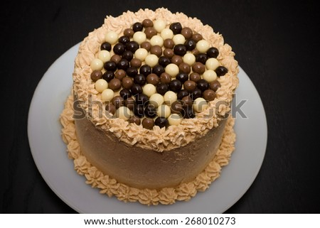 caramel cake with chocolate balls crisp in several flavors - stock photo