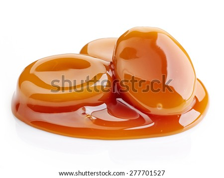 caramel candies and sweet sauce isolated on white background - stock photo