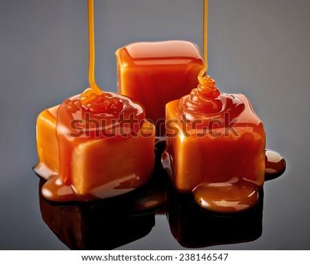 caramel candies on black background - stock photo