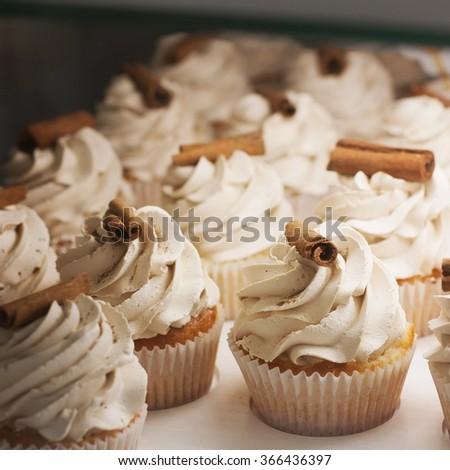 Caramel cupcakes decorated with cinnamon sticks - stock photo