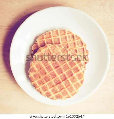 Caramel dutch waffle on dish with retro filter effect - stock photo