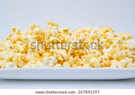 caramel popcorn grains on the white dish and white background - stock photo