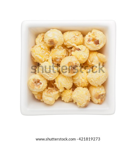 Caramel popcorn in a square bowl isolated on white background - stock photo