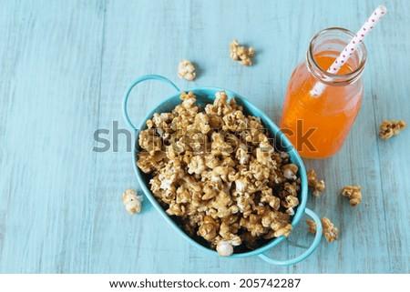 Caramel popcorn snack in blue tin bucket with orange soda pop with straw - stock photo