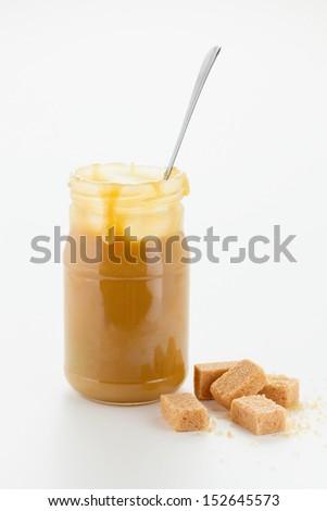 Caramel sauce in jar with sugar cubes - stock photo