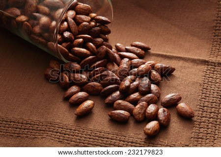 CAramelized almond nuts falling out of jar - stock photo