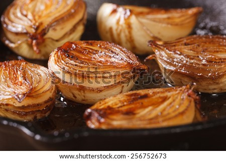 Caramelized onion halves with balsamic vinegar in a pan close-up, horizontal  - stock photo