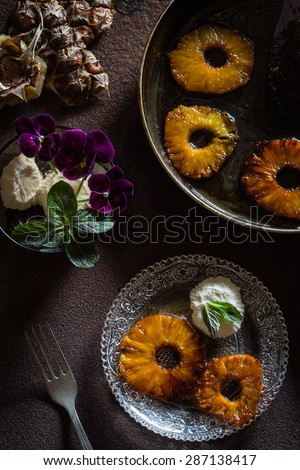Caramelized Pineapple Slices with Frozen Yogurt and Fresh Mint Leaves. Rusty Iron Surface. Overhead View - stock photo