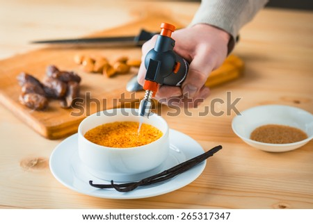 Caramelizing of creme brulee with bourbon vanilla sticks and hand with torch - stock photo