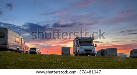 Caravans and cars parked on a grassy campground in summer under beautiful sunset - stock photo
