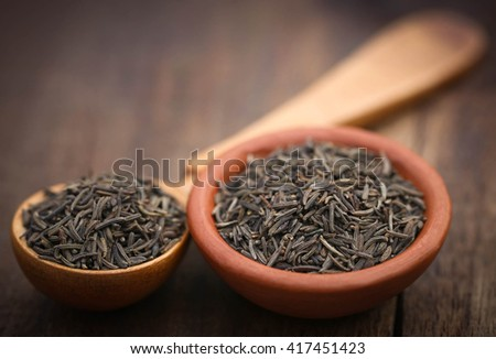 Caraway seeds in a wooden spoon and bowl - stock photo