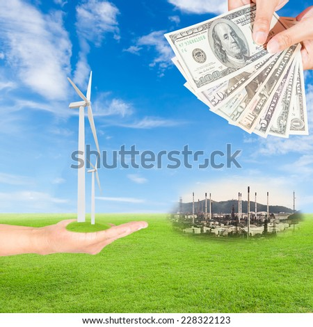 Carbon credits concept,hand holding wind turbine and US Dollars banknote with oil refinery plant against green field and blue sky background - stock photo