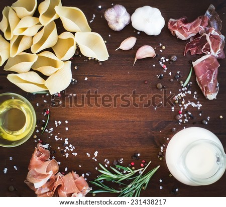 Carbonara pasta ingredients: conchiglioni, bacon, a jug of cream, olive oil, garlic, fresh herbs and spices on a dark wood background with a copy space in the center - stock photo
