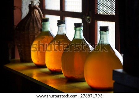Carboys with hand made liqueur - stock photo