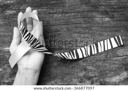 Carcinoid Cancer Awareness ribbon zebra stripe pattern  helping hand & old aged wood background: Satin fabric loop symbolic logo raising support help people life living w/ tumor illness  - stock photo