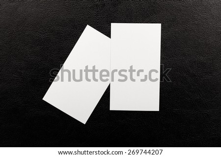Card. Blank business cards with rounded corners on a black leather background - stock photo