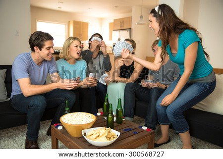 Card playing poker game night friends winner celebrating victory losers frowning - stock photo