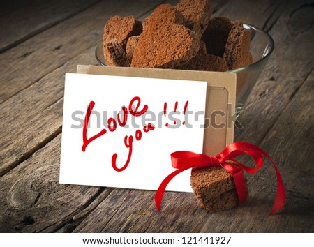 Card with Message Love You in the Letter and Chocolate Cookies in the Shape of Heart - stock photo