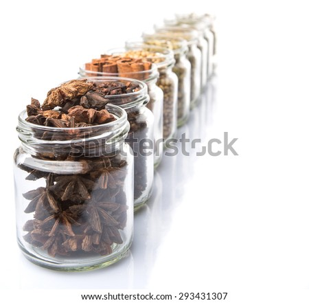 Cardamom, star anise, cinnamon, clove, coriander seed spices and dried bay leaves, parsley, thyme, rosemary herbs in mason jars over white background - stock photo