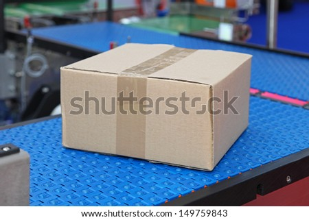 Cardboard box at conveyor rollers in distribution warehouse - stock photo