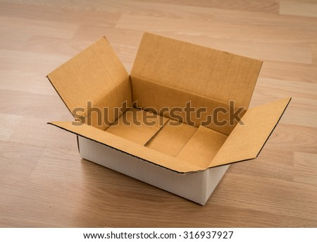 Cardboard box on wood - stock photo
