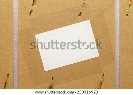 Cardboard Box with Large Staples, Plastic Straps and Blank Label. - stock photo