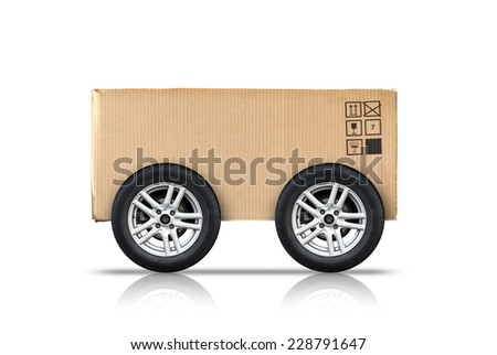 Cardboard box with standard signs and automotive wheels isolated on white background, fast delivery concept metaphor  - stock photo