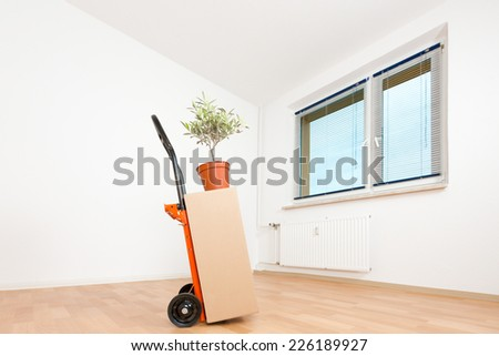 cardboard boxes in an empty apartment. moving to a new apartment Hand Truck - stock photo