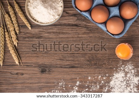 Cardboard egg box, flour and ears on wooden table. Top view with copy space - stock photo