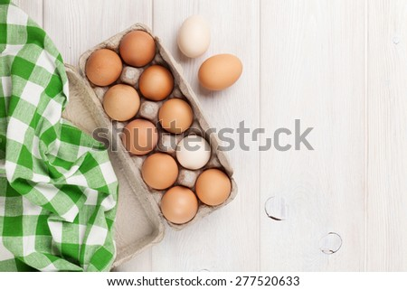 Cardboard egg box on wooden table. Top view with copy space - stock photo